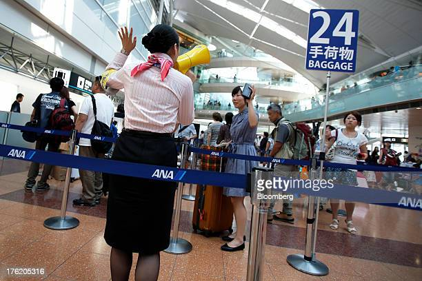 An All Nippon Airways Co employee assists passengers with checkin baggage at Haneda Airport in Tokyo Japan on Sunday Aug 11 2013 Japan's gross...