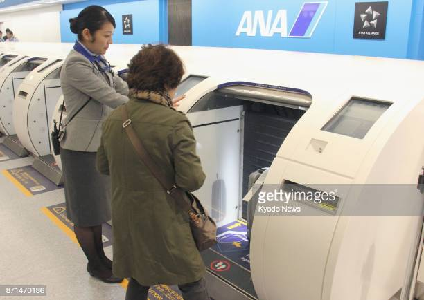 An All Nippon Airways ground crew helps a passenger use a selfservice baggage dropoff machine at New Chitose airport in Sapporo northern Japan on Nov...