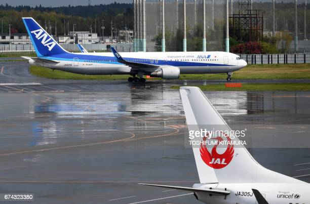 An All Nippon Airways plane taxis beside a Japan Airlines plane at Narita International airport in Narita on April 28 2017 The parent of Japanese...
