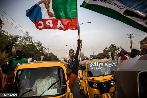 An All Progressives Congress Party supporter waves a party flag while celebrating initial results released by the Nigerian Independent National...