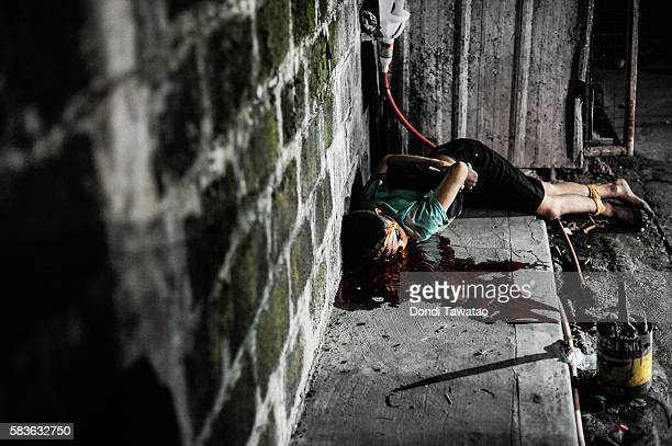 An alleged drug dealer and victim of a summary execution with hands bound and his head wrapped in tape lie on a road on July 27 2016 in Manila...