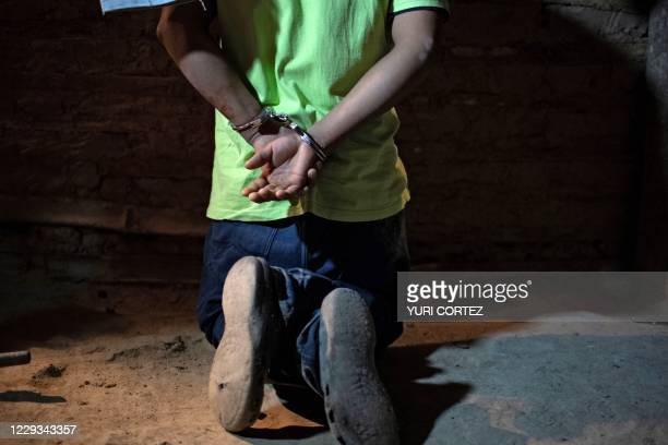 An alleged gang member remains kneeling and handcuffed while being arrested by agents of the operational tactical section of the National Civil...