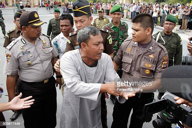 An alleged law violator is taken to the publicly whipping ceremony at Meulaboh on February 12 2016 in West Aceh Indonesia About 32 men in Aceh were...