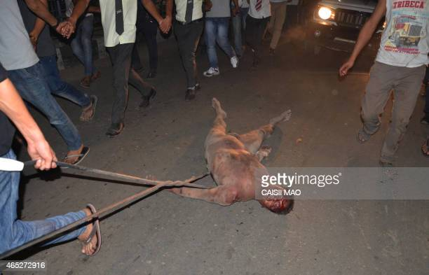 An alleged rapist is dragged on a street by a crowd of Indian men after he was pulled out of prison and beaten to death in Dimapur in the...