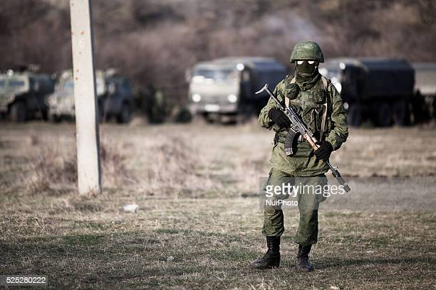 An alleged Russian soldier in full body armor and armed with an assault rifle standing in front of the besieged Ukrainian Military Base in...