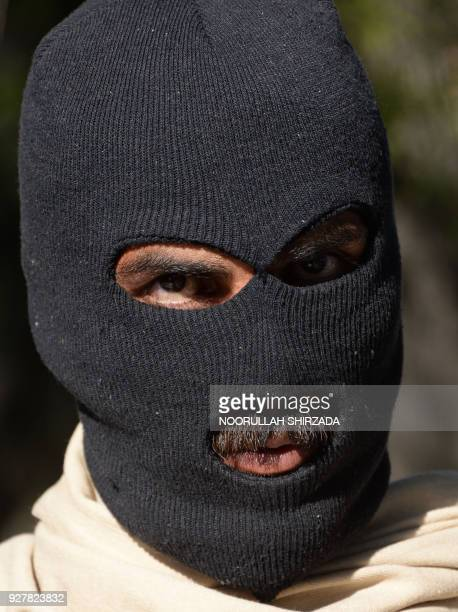 An alleged Taliban fighter stands handcuffed while being presented to the media at a police headquarters in Jalalabad on March 6 2018 Afghan police...
