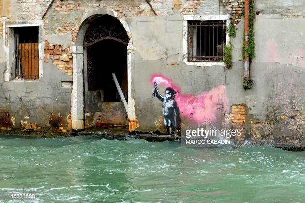 TOPSHOT An alleged work by British street artist Banksy depicting a migrant child wearing a lifejacket holding a pink flare is painted on the outer...