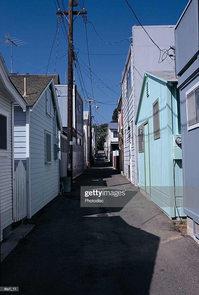 an alley runs between blue houses under a blue sky with telephone poles rising from the street : Foto de stock
