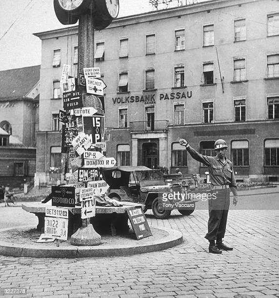 An Allied Forces military policeman directs traffic in the square at the center of Passau Germany during the Allied occupation of Germany at the end...