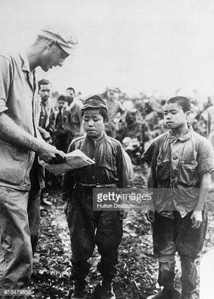 An Allied forces soldier questions Japanese prisoners after their capture near Okinawa   Location Near Okinawa Prefecture Japan
