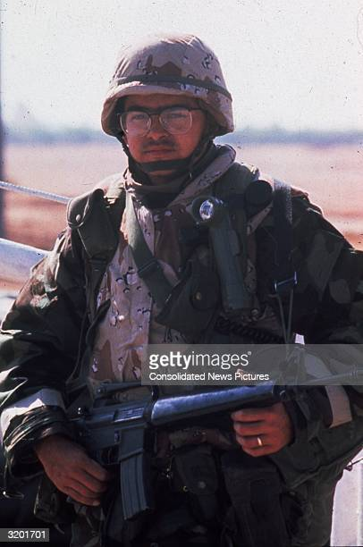 An Allied soldier poses with his rifle during Operation Desert Storm in the Persian Gulf War He wears a helmet and fatigues
