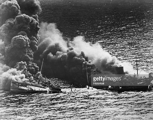 An allied tanker crumbles under the heat of fire after being torpedoed in the Atlantic Ocean by a German submarine. 1942.