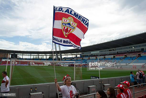 An Almeria fan holds up her team's flag ahead off the La Liga match between UD Almeria and FC Barcelona on September 28 2013 in Almeria Spain