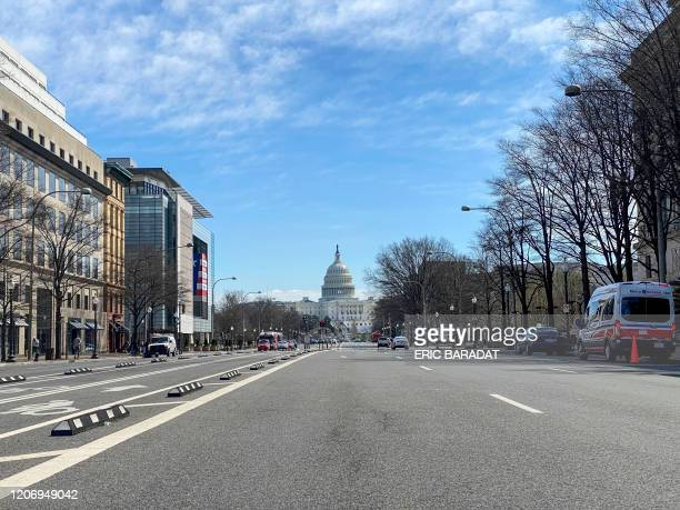 An almost empty Pennsylvania Avenue is seen at noon in Washington DC on March 13 2020 Fear of the coronavirus spread reduced traffic and usual...