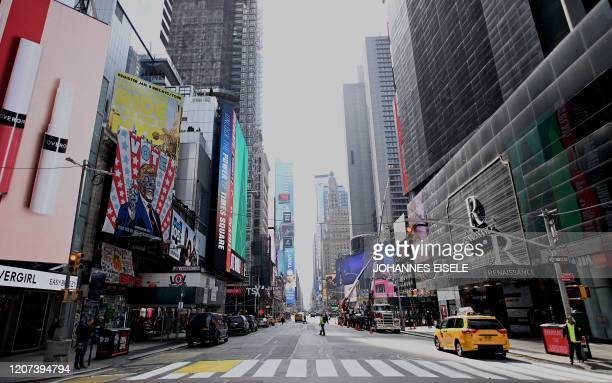An almost empty street is seen at Times Square in Manhattan on March 16, 2020 in New York City. - Stocks tumbled on March 16, 2020 despite emergency...