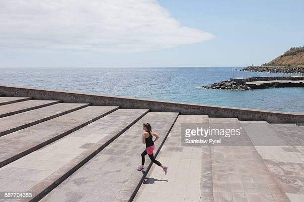 An alone girl running up large stairs near ocean