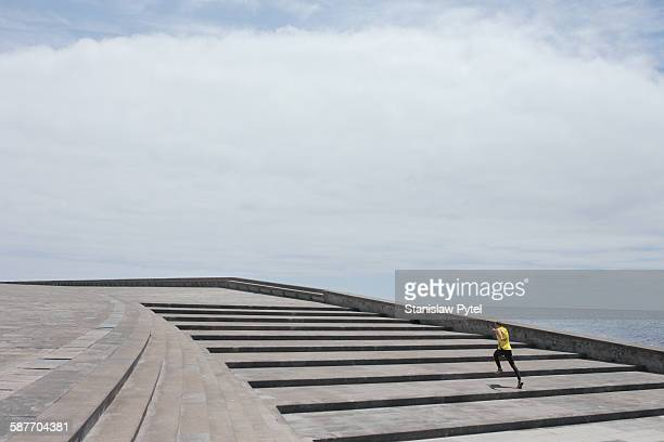 An alone man running up large stairs