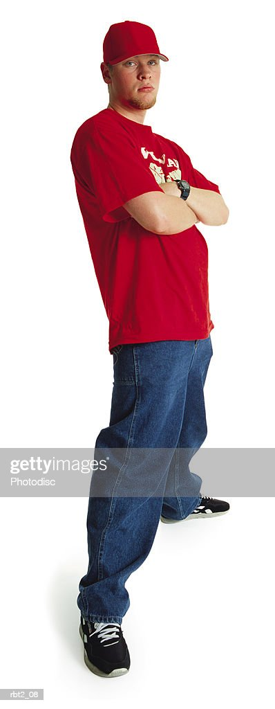 an aloof young caucasian man with a goatee wearing a red baseball hat and teeshirt stands obstinately with arms crossed : Foto de stock