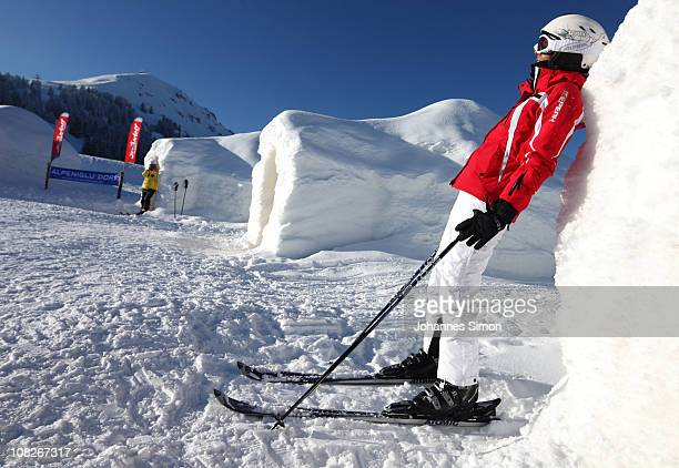 An alpine skier enjoys the sun leaning against a sleeping igloo of the Alpeniglu hotel at Hochbrixen on January 23 2011 in Brixen im Thale Austria...