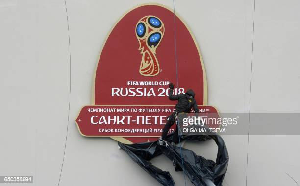 An alpinist removes a wrap from the FIFA World Cup 2018 logo before a ceremony marking the last 100 days until the start of the FIFA Confederations...