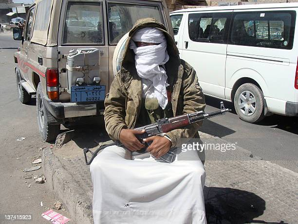 An alQaeda militant sits with his gun in the city of Rada 130km southeast of the Yemeni capital Sanaa on January 20 2012 An AlQaeda fighter was...