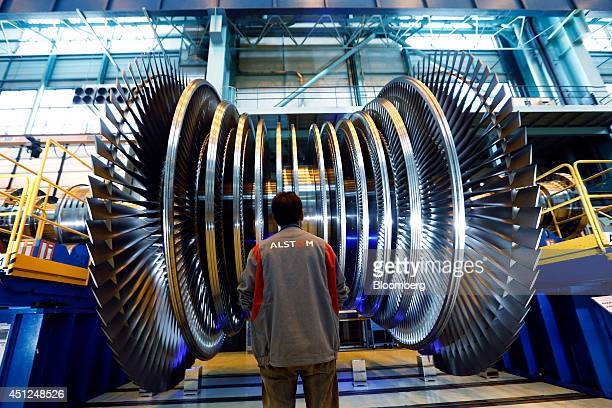 An Alstom employee stops and checks a turbine unit under construction inside Alstom SA's powergeneration plant in Belfort France on Tuesday June 24...