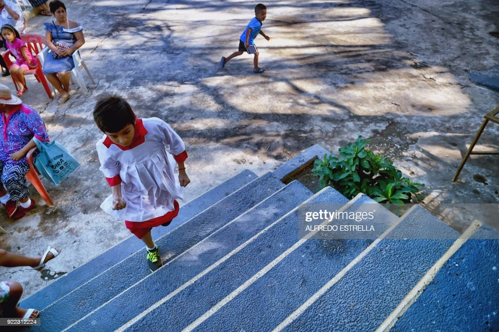 A an altar boy climbs the stairs before a mass at Kilometro 30 community near the Acapulco resort in Guerrero State, Mexico on February 14, 2018. Violence in the state of Guerrero claimed the lives of two priests on February 5, 2018. / AFP PHOTO / Alfredo ESTRELLA / TO