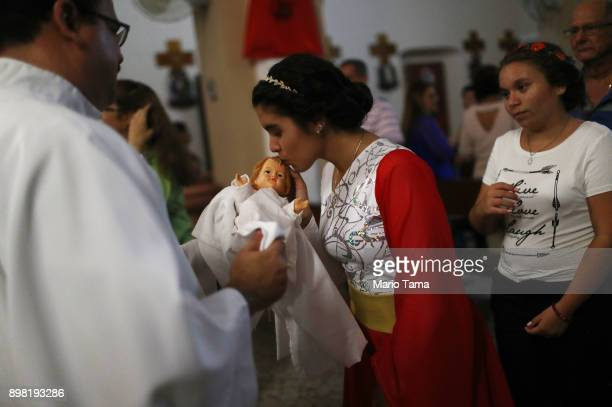 An altar server kisses a doll depicting Jesus Christ during 'midnight mass' at the Nuestra Senora Del Carmen Church on Christmas Eve on December 24...