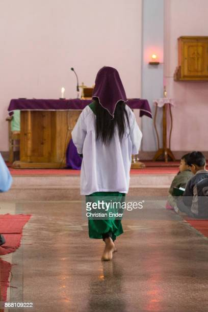An altar server walks barefoot towards the altar while a ceremony inside a church in Kalimpong