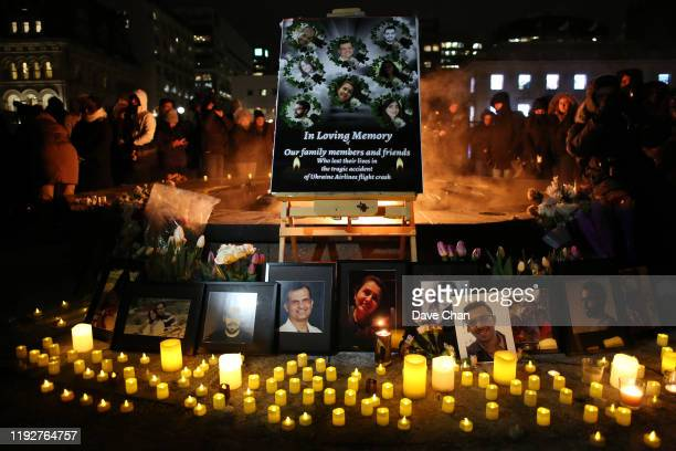An altar with photographs of the victims who were killed in a plane crash in Iran is seen as people gather around to held a vigil in their memories...