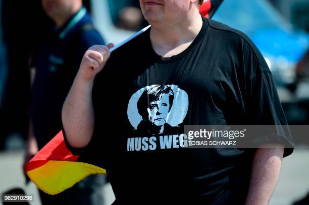 An Alternative for Germany 's demonstrators wearing a tshirt reading 'must go' under a portrait of German Chancellor Angela Merkel gather at the main...