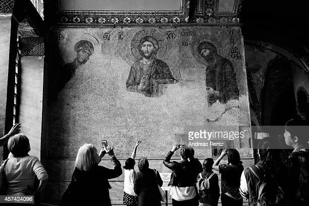 An alternative view of tourists taking pictures of a mosaic inside Hagia Sophia on October 18 2014 in Istanbul Turkey