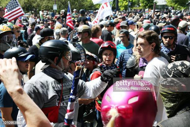 An altright sympathizer knocks the hat off an opponents head as altright activists antifascist protestors and people on all sides of the political...