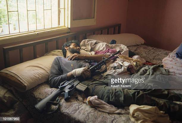 An Amal militia man sleeps while holding his M16 automatic assault rifle after combatting with Palestinians in Bourj elBarajneh Palestinian refugee...