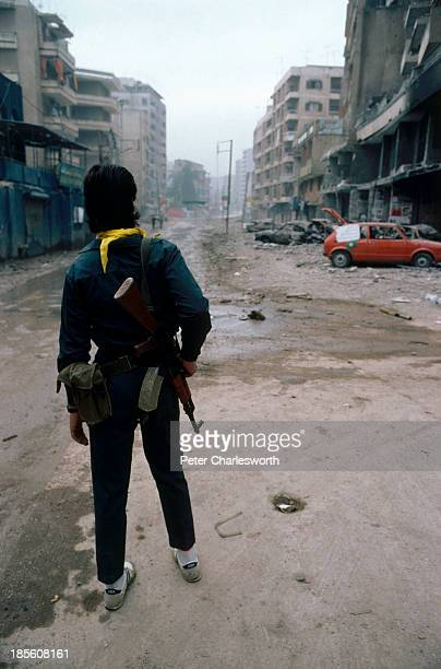 An Amal Shi'ite militiaman with his AK47 moves down a deserted street in the southern suburbs of Beirut during heavy random shellling from Phalangist...