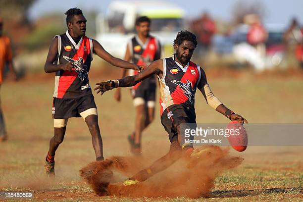 An Amata player kicks the ball during the Far North West Sports League football grand final between Amata in black and Wintjalangu in white on...