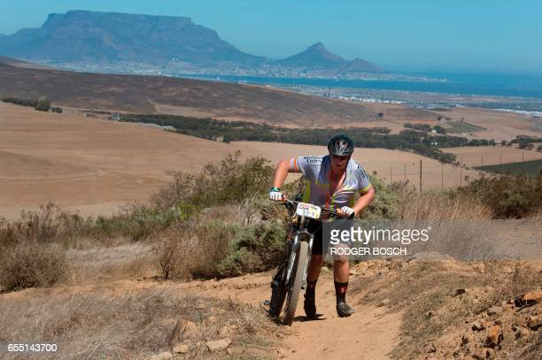 An amateur cyclist walks up a steep hill through wheat fields during the prologue stage of the 2017 Cape Epic mountain bike stage race near...