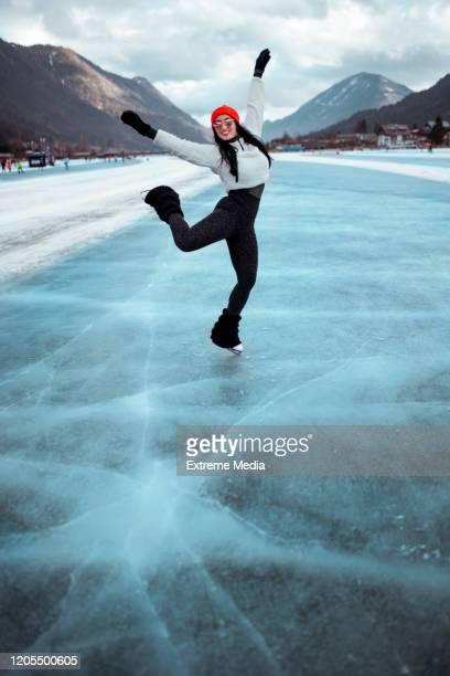 eine amateur-skaterin, die beim skaten auf dem zugefrorenen see wirbel und figuren macht - eiskunstlauf stock-fotos und bilder
