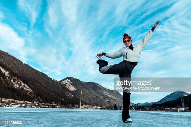an amateur figure skater practicing on a frozen lake surface during winter time - figure skating stock pictures, royalty-free photos & images