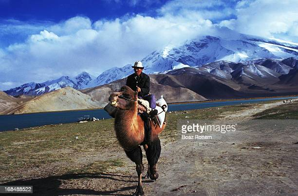 An amazing moment in Karakul lake in the Pamir mountains. China A Kyrgyz man riding his bactrian camel.