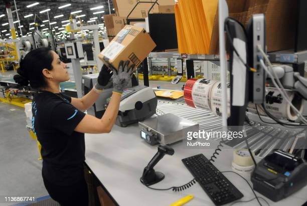 An Amazon associate processes a package for delivery at the newest Amazon Robotics fulfillment center during its first public tour on April 12 2019...