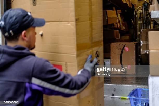 An Amazon box sits in front of a driver for an independent contractor to FedEx Corp unloading packages from a delivery truck in New York US on Monday...