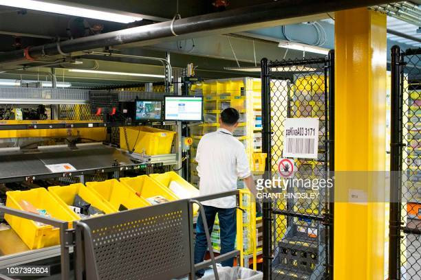 An Amazon employee pulls goods from robotic shelves during a tour of Amazon's Fulfillment Center September 21 2018 in Kent Washington
