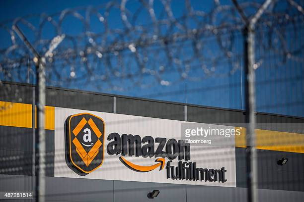 An Amazon Fulfillment logo sits on display beyond a security fence topped with razor wire outside the new AmazonCom Inc fulfillment center on its...