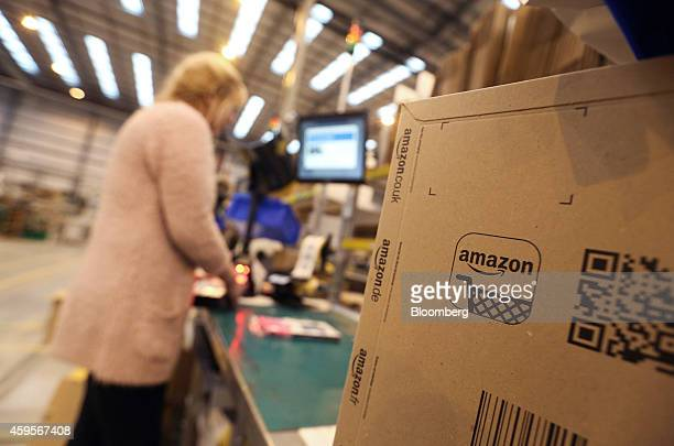 An Amazon logo sits on a cardboard delivery box as an employee processes customer orders ahead of shipping at one of Amazoncom Inc's fulfillment...