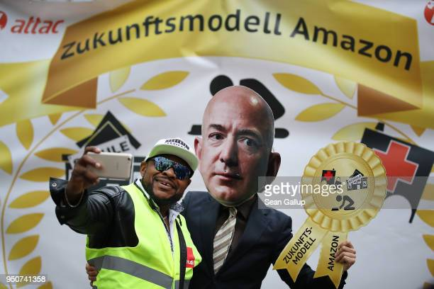 An Amazon warehouse worker shoots a selfie with an activist dressed as Amazon CEO Jeff Bezos during a protest gathering outside the Axel Springer...