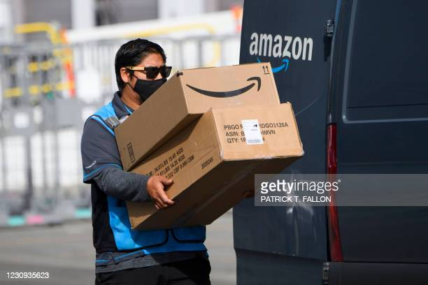 An Amazon.com Inc. Delivery driver carries boxes into a van outside of a distribution facility on February 2, 2021 in Hawthorne, California. - Jeff...