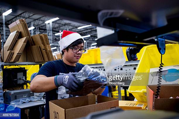 An Amazoncom Inc employee loads merchandise into a box at the company's fulfillment center ahead of Cyber Monday in Tracy California US on Sunday Nov...
