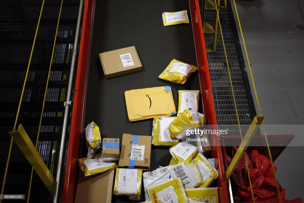 An Amazon.com Inc. package moves down a conveyor belt while being sorted at the DHL Worldwide Express hub of Cincinnati/Northern Kentucky International Airport in Hebron, Kentucky, U.S., on Wednesday, Aug. 16, 2017. The Deutsche Post AG, parent company to Worldwide Express, second-quarter operating profit jumped 12 percent as the German mail operator handled more express deliveries and won more business at its logistics unit. Photographer: Luke Sharrett/Bloomberg via Getty Images