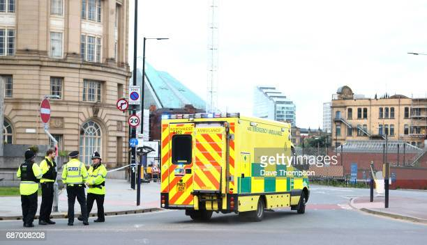 An ambulance arrives as police officers stand at the Miller Street and Corporation Street Crossroads near the Manchester Arena on May 23 2017 in...